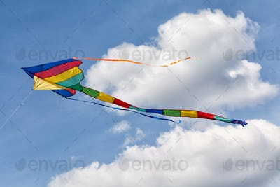 Colorful kite flying in the cloudy sky. Summer holidays concept. Retro style colors