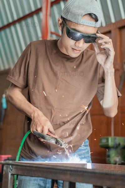 Welders wear black welding goggles when welding iron rods
