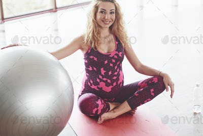 Smiling blonde pregnant woman in pink sitting on the fitness mat holding the stability ball