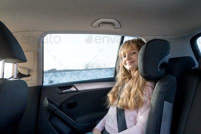 Smiling joyful little girl looking at camera sitting in car seat