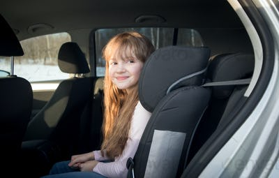 Cute little girl sitting in child car seat on the back of car