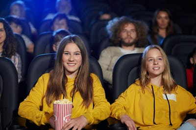 Young laughing female teenagers in movie theater