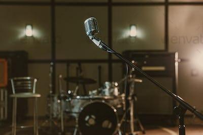 vintage microphone on stand against blurred drum set