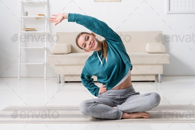 smiling girl sitting in lotus position on yoga mat and stretching at home