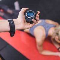 cropped shot of woman doing plank while trainer holding stopwatch on foreground