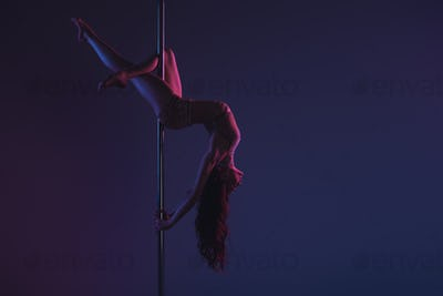 beautiful sensual flexible girl exercising with pole on blue