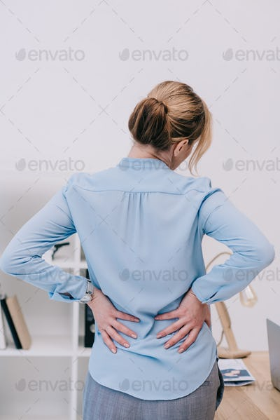 rear view of overworked businesswoman with backpain leaning on table at office