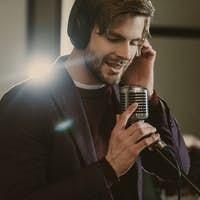 handsome young singer in headphones performing song at studio