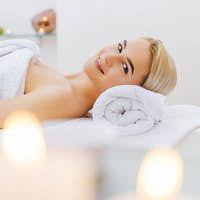 smiling young woman relaxing on massage table at spa salon
