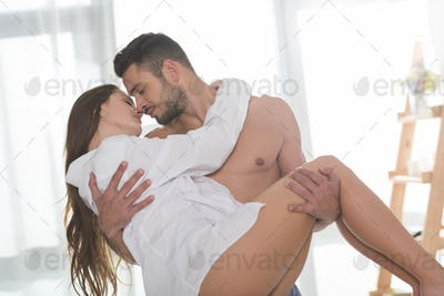 handsome shirtless man carrying his beautiful girlfriend in white shirt