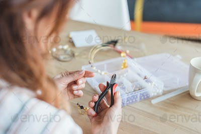 close-up shot of young woman making accessory with linesman pliers in workshop