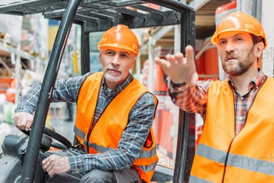 worker and his senior colleague working with forklift machine in storehouse