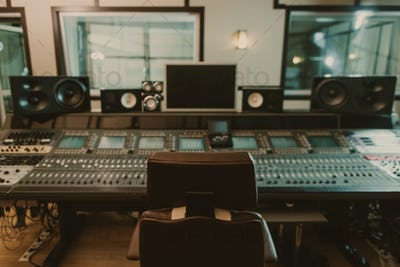 view of sound producing equipment at recording studio with armchair on foreground
