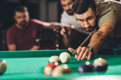 young handsome man playing in pool with friends at bar