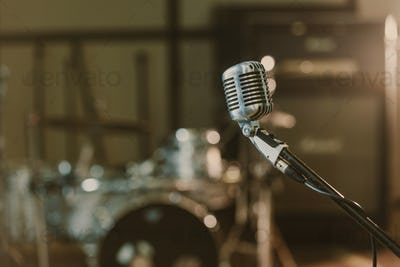 close-up shot of vintage microphone on stand against blurred drum set