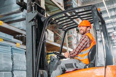 male worker in safety vest and helmet sitting in forklift machine in storage