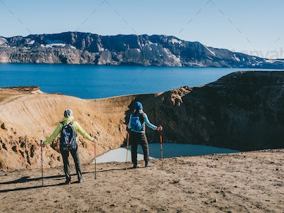 hikers looking at Geothermal crater lake near the Askja volcano, Iceland