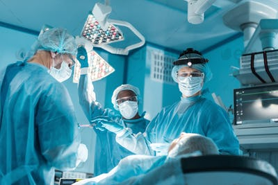 multicultural surgeons and patient during surgery in operating room