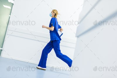 hurry female surgeon in medical masks with diagnosis running in hospital corridor