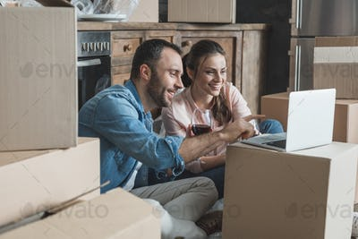 happy couple drinking wine and using laptop in new house