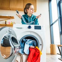 young woman leaning at broken washing machine