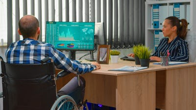 Entrepreneur in wheelchair analysing financial statistics