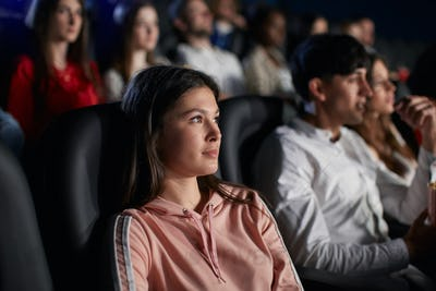 Young girl enjoying free time in movie theater