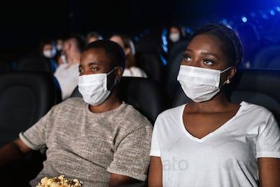 African couple wearing face masks enjoying time in cinema