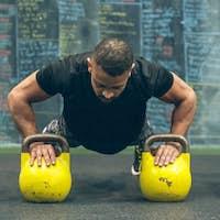 Sportsman doing push-ups with kettlebells