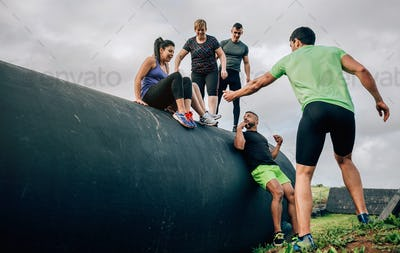 Participants in an obstacle course going down a drum