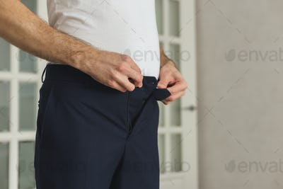 Overweight man trying to fasten small pants, grow stout man