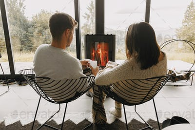 Stylish couple in sweaters with warm tea relaxing at modern fireplace with view on mountains
