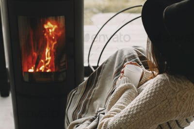 Stylish woman holding warm cup of tea and relaxing at modern fireplace with view on mountains