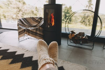 Feet in warm cozy socks on background of modern  fireplace and window with view on mountains