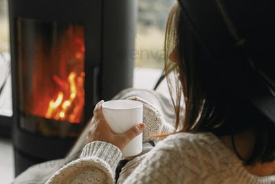 Stylish woman in knitted sweater relaxing with warm cup of tea at modern fireplace, closeup