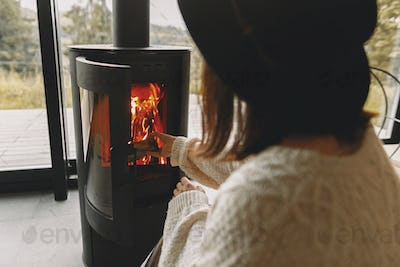 Stylish woman in knitted sweater putting firewood to modern black fireplace with warm fire