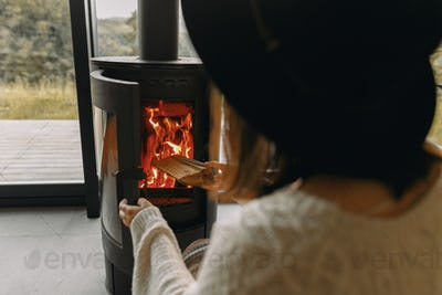 Stylish woman in knitted sweater putting firewood in to modern black fireplace with warm fire