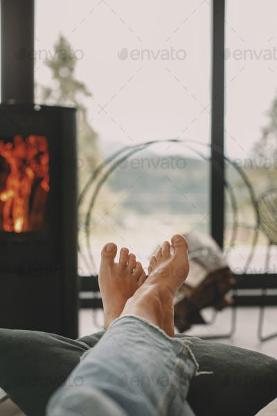 Woman barefoot relaxing in comfortable home, cozy warm moments. Feet at modern fireplace and window