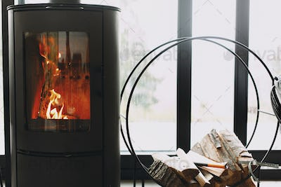 Modern black fireplace with fire and firewood on metal stand at window with view on mountains