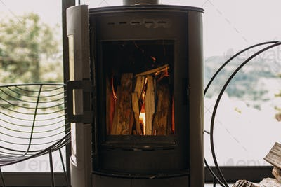 Modern black fireplace with burning fire and firewood on metal stand. Cozy warm moments