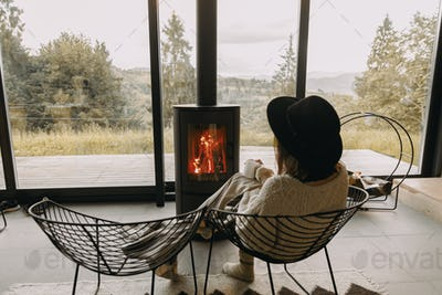 Stylish woman in sweater and hat holding warm cup of tea at modern black fireplace. Cozy home