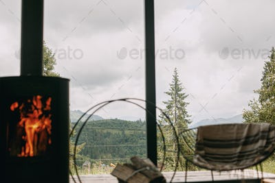 Beautiful view on mountains hills and trees through window cabin with fireplace