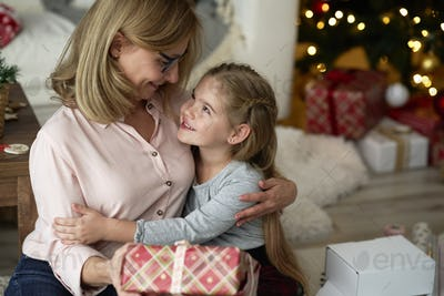 Grandmother giving her little granddaughter a Christmas gift