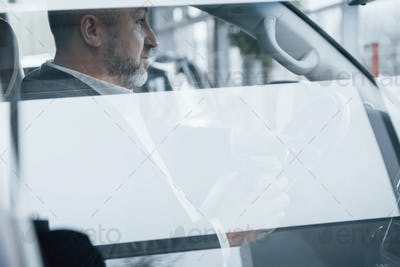 Through the glass. Side view of senior businessman in official clothes inside of modern car