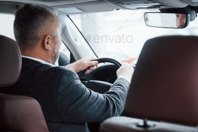 View from behind of senior businessman in official clothes driving a modern new car