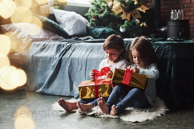 Christmas holidays with gifts for these two kids that sitting indoors in the nice room near the bed