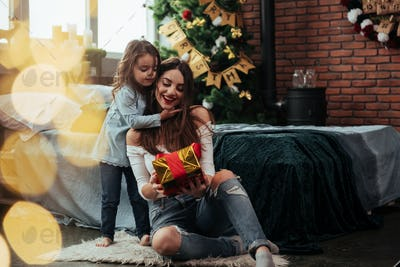 Look what I have for you. Mother and daughter sits in holiday decorated room and holds gift box