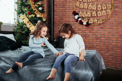 Child smiles. Kids sits on the bed with decorative background. Conception of new year