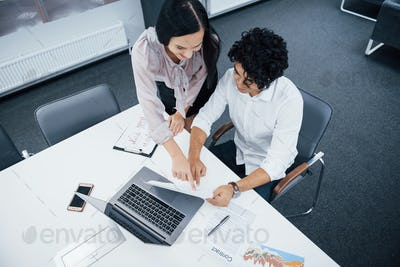 Top view. Cheerful coworkers in a modern office smiling when doing their job using laptop
