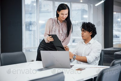 Curly guy and brunette girl discusses the details of the contract in modern office